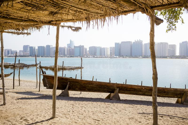 Wooden boat at the Heritage Village, in front of the Abu Dhabi skyline, UAE royalty free stock photo