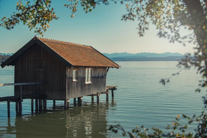 House on stilts over lake. Wooden boat house on stilts on lake front stock photo