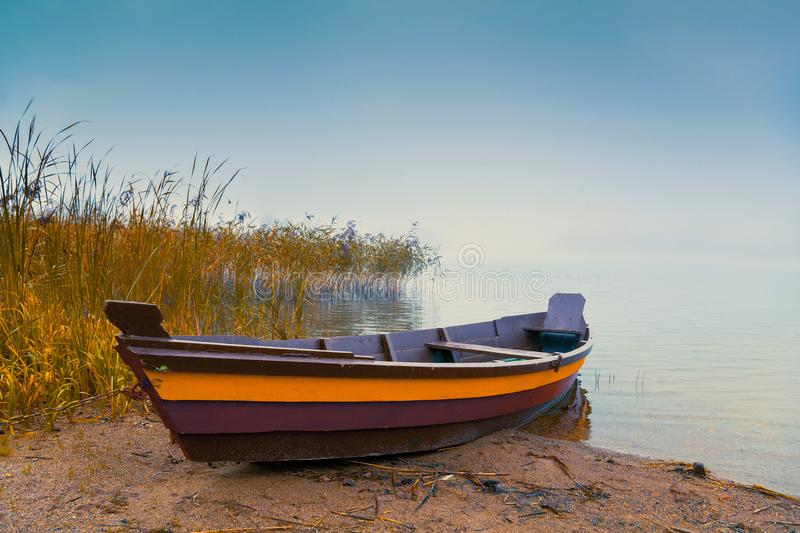 Wooden boat on the lake shore stock photo
