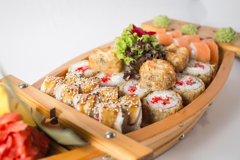 Wooden boat with lots of sushi with ginger and wasabi royalty free stock photo
