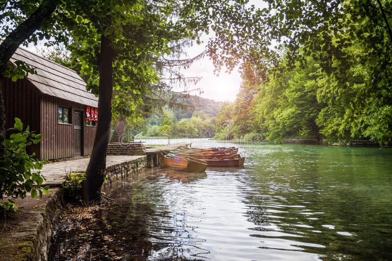 Wooden boat at the pier on the beautiful clear lake in the woods. Plitvice, National Park, Croatia stock photo
