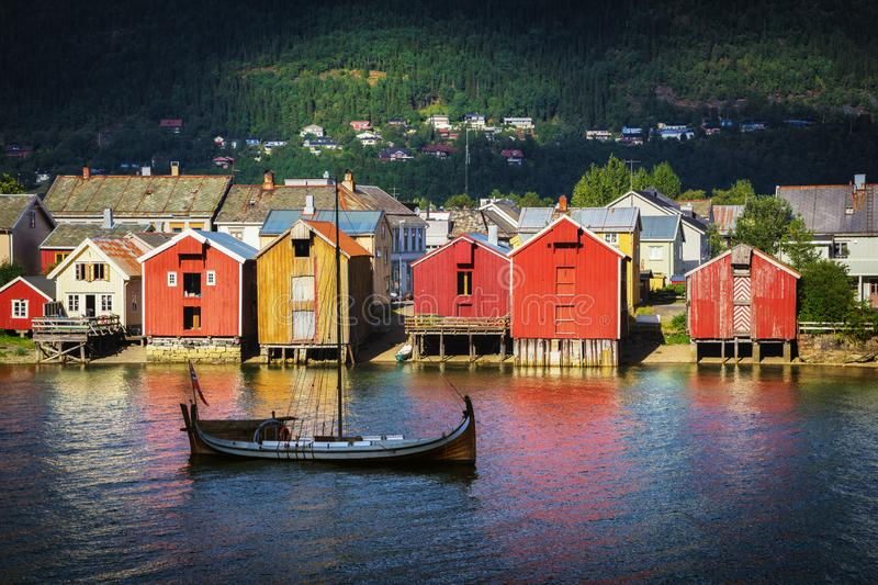 Wooden boat on a river, colorful harbor buildings royalty free stock photo