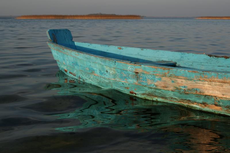 Old wooden boat of blue color. Water reflections. royalty free stock photos