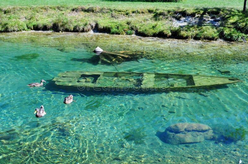 Wooden boat submerged under water. Salzkammergut. Austria royalty free stock photography