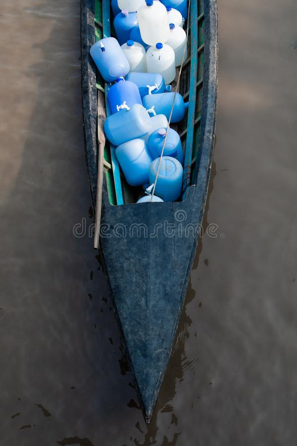 Wooden boat transporting bottles with fresh drinking water in Nyaung Shwe, Myanmar royalty free stock photo
