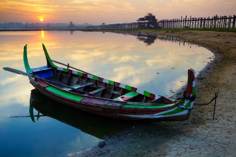 Wooden boat in Ubein Bridge at sunrise, Mandalay, Myanmar. (World longest wooden bridge stock photography