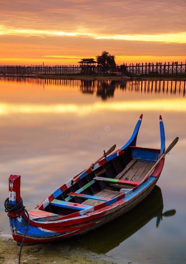 Wooden boat in Ubein Bridge at sunrise, Mandalay, Myanmar. (World longest wooden bridge stock images