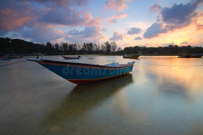 Wooden boat in water at sunset royalty free stock images