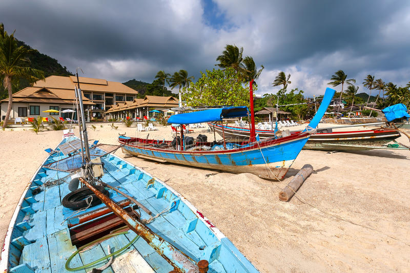 Wooden boats of Asia on the sandy beach of the resort. Wooden boats of blue color on the sandy beach. And the hotel building with palm trees royalty free stock photos