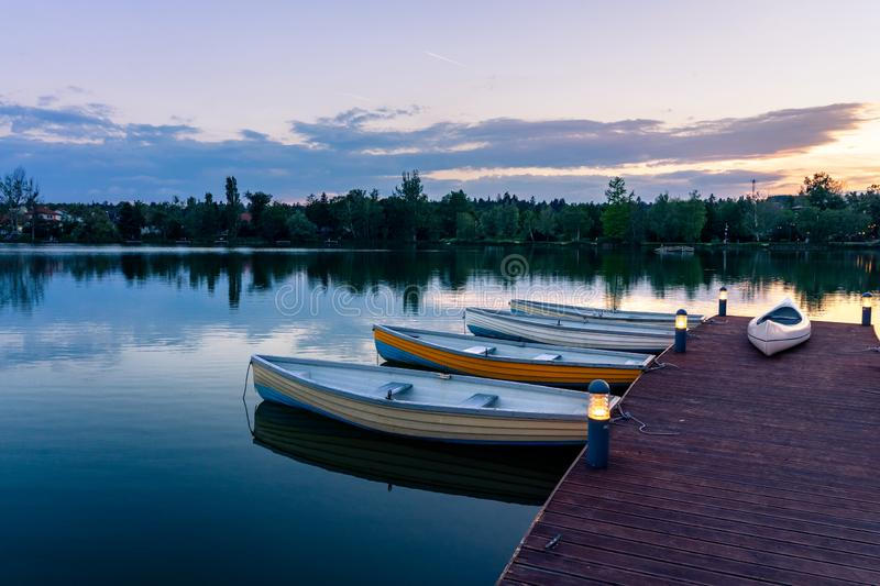 Wooden boats on a calm lake called Csonakazo Lake in Szombathely Hungary at dusk after sunset. Next to the pier deck stock photo