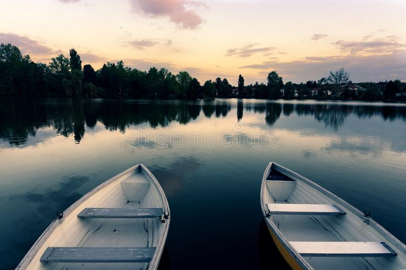 Wooden boats on a calm lake called Csonakazo Lake in Szombathely Hungary at dusk after sunset. Next to the pier deck stock image