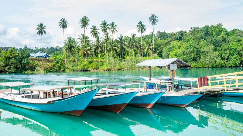 Wooden boats docked at the port. beautiful view of beach with clear blue water and coconut tree, royalty free stock images