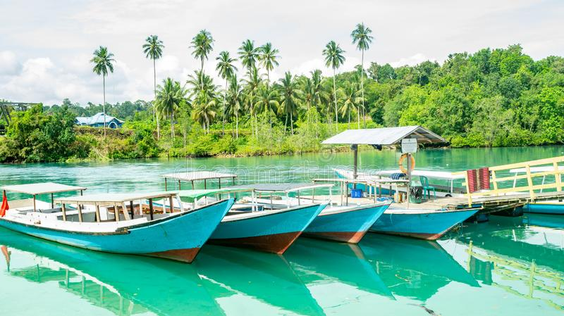 Wooden boats docked at the port. beautiful view of beach with clear blue water and coconut tree, royalty free stock photo