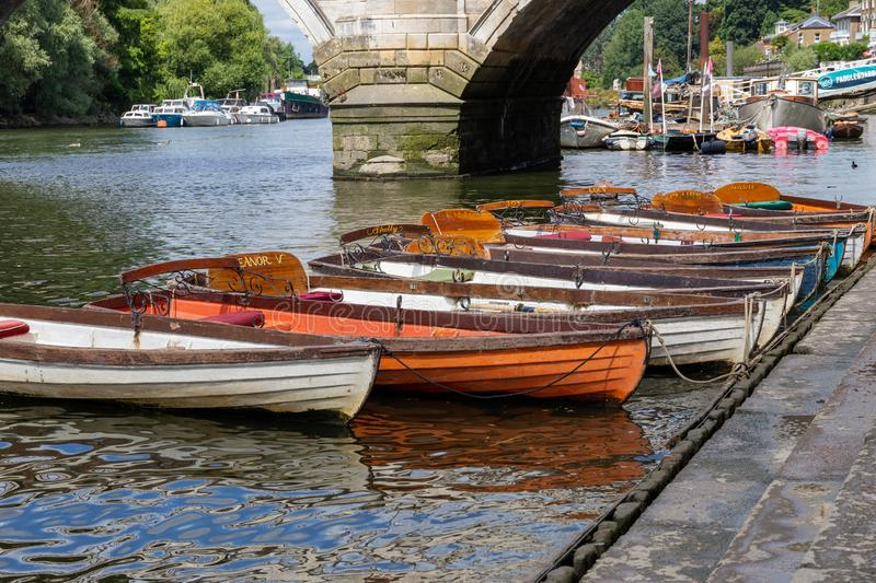 Richmond boats for hire moored on the River Thames. LONDON, UK - JULY 02, 2019. Wooden boats of Richmond Bridge Boat Hire company moored on the River Thames royalty free stock photos