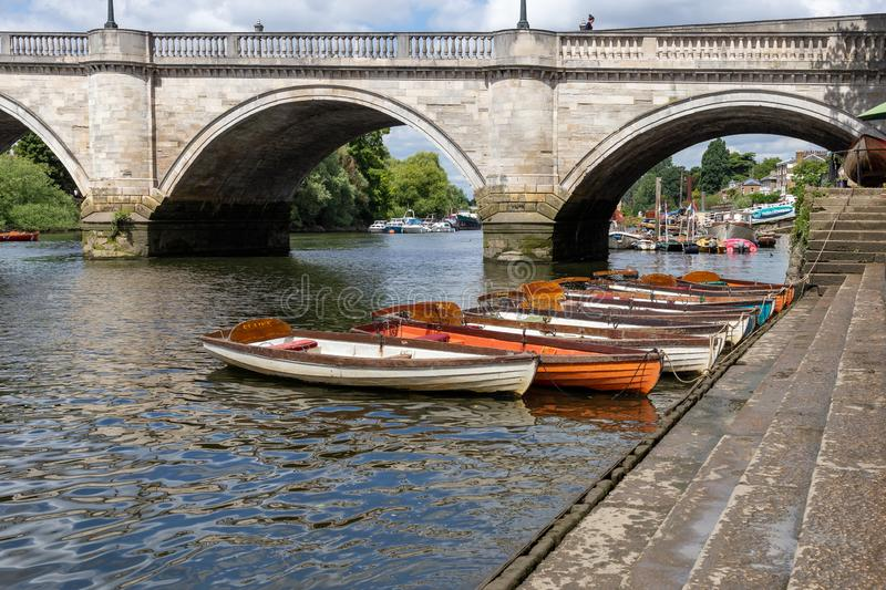 Richmond boats for hire moored on the River Thames. LONDON, UK - JULY 02, 2019. Wooden boats of Richmond Bridge Boat Hire company moored on the River Thames royalty free stock image