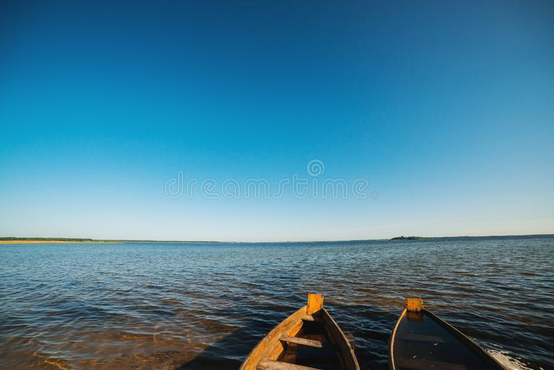 Wooden boats on the lake. Beautiful landscape. Summer vacation. Two boats on the lake against the blue sky stock photography