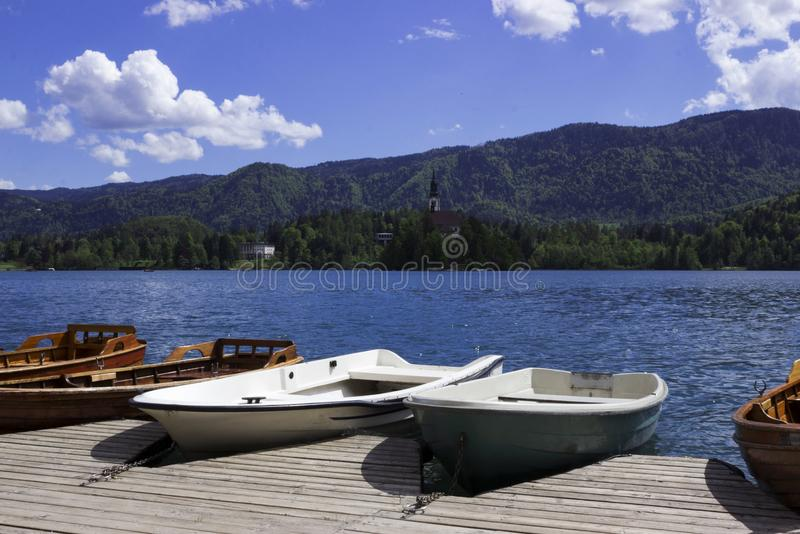Wooden boats on the pier on the background of the castle on Lake Bled. Beautiful view, nature, calm.  royalty free stock image