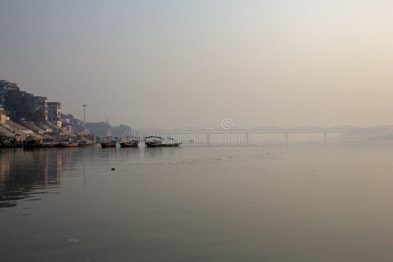 Wooden boats at sacred river Ganges in Varanasi, India. Malviya. Bridge in the background, India royalty free stock photo