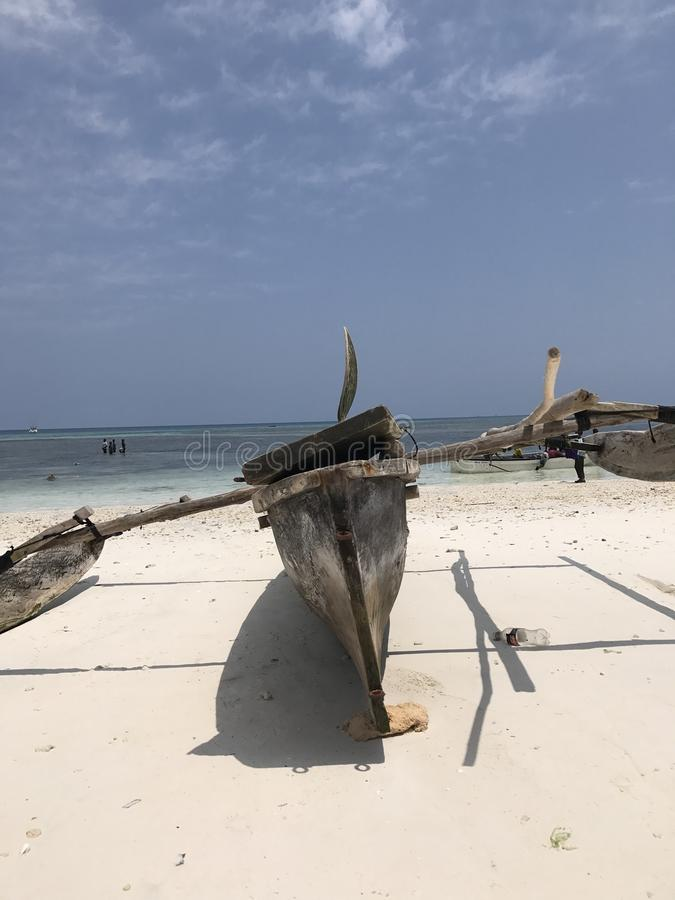 A classic wooden boat sits on the shores of Zanzibar. Wooden boats in Tanzania are both useful and decorative for the locals and tourists. Zanzibar sits on the stock photography