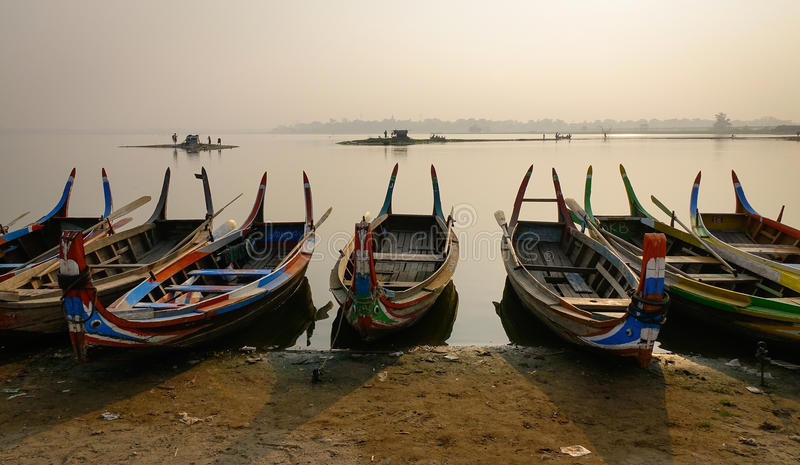 Wooden boats on lake in Mandalay, Myanmar. Wooden boats waiting passengers on lake at sunset in Mandalay, Myanmar stock photos