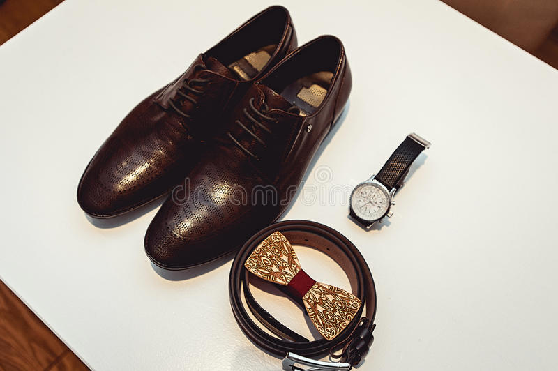 Wooden bow tie, brown leather shoes, belt, watch. Grooms wedding morning. Close up of modern man accessories. Close up of modern man accessories on a white stock photo