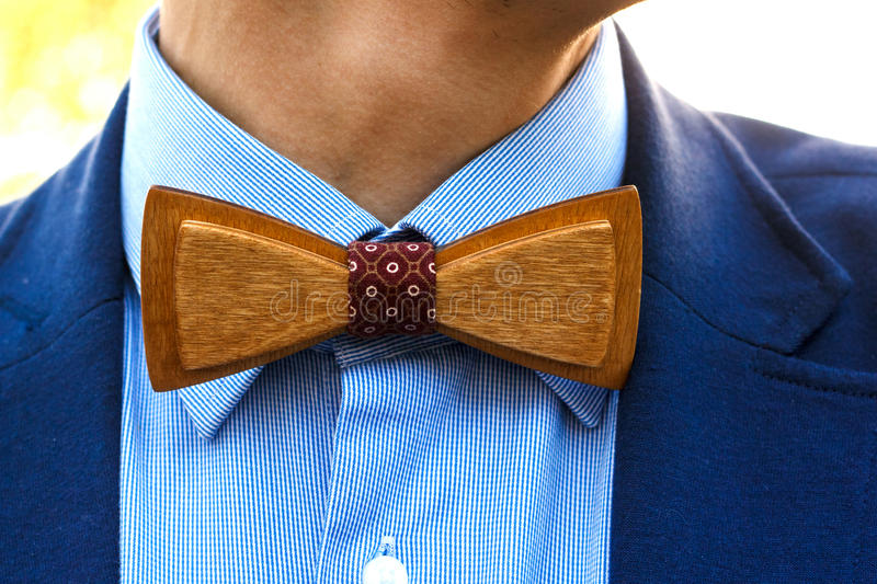 Wooden bow tie. Fashionable wooden bow tie closeup. Retro style gentleman in blue woollen suit at wedding event royalty free stock images