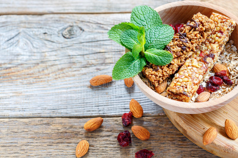 Wooden bowl with bars of cereal, nuts, dried fruit and mint. stock photos