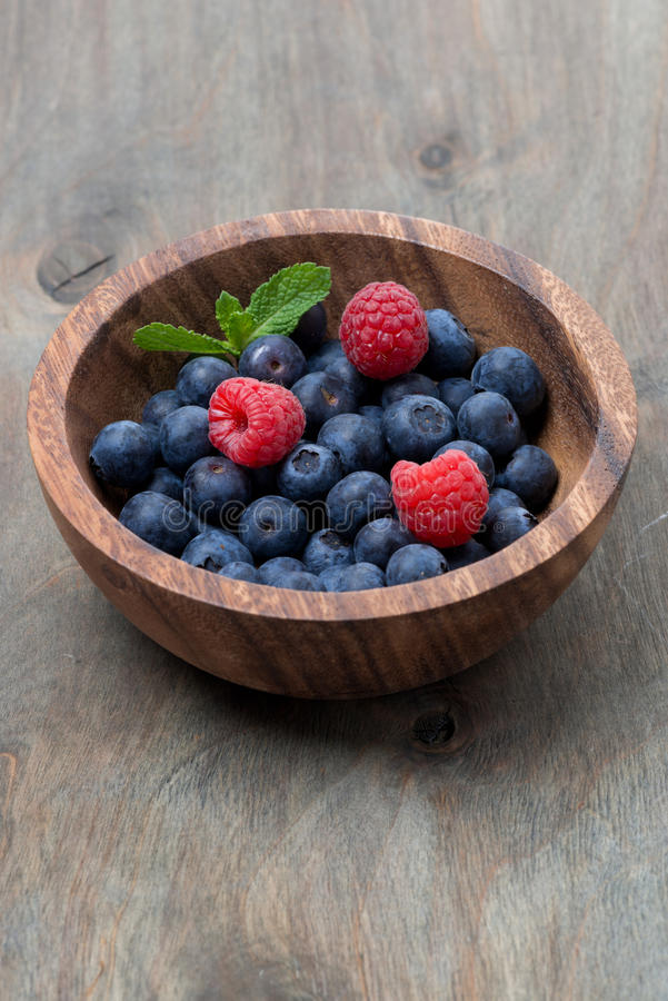Wooden bowl with blueberries and raspberries stock photos