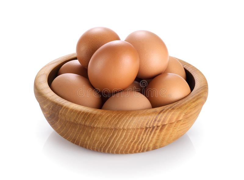 Wooden bowl with eggs isolated on white background. stock photos
