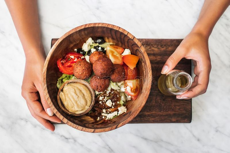 Wooden bowl with falafel balls in woman hands. Wooden bowl with falafel balls, hummus and fresh salad. Woman hands holding olive oil on side. White marble royalty free stock photo