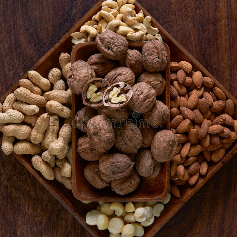 A wooden bowl full of walnuts, peanuts, almonds, cashews and macadamias on a wooden board stock images
