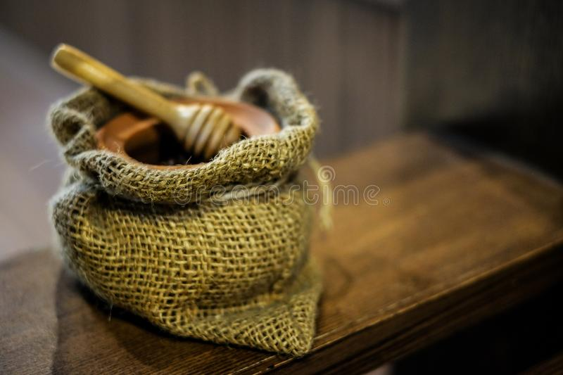 Wooden bowl for honey bee with sack bag & wooden honey dipper. stock images