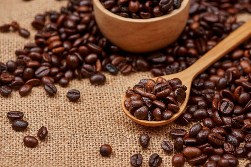Wooden bowl with roasted coffee beans on rustic background. stock photos