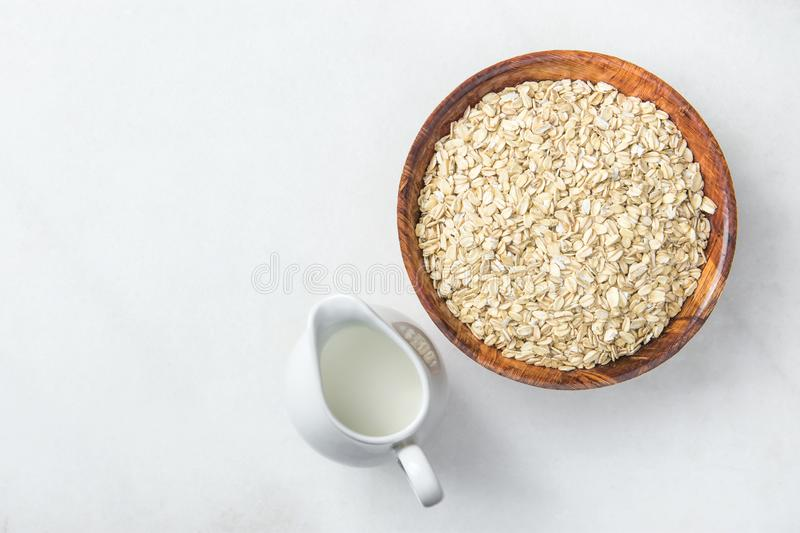 Wooden Bowl with Rolled Oates Jug with Milk on White Marble Stone Table. Balanced Healthy Diet Fiber Nutrition Concept royalty free stock image