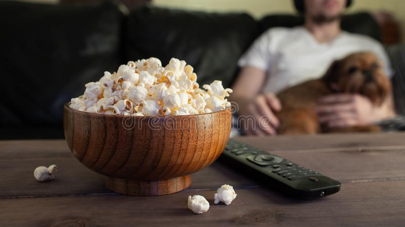 Wooden bowl with salted popcorn and TV remote on wooden table. In the background, a man with a red dog watching TV on the couch.  royalty free stock photos