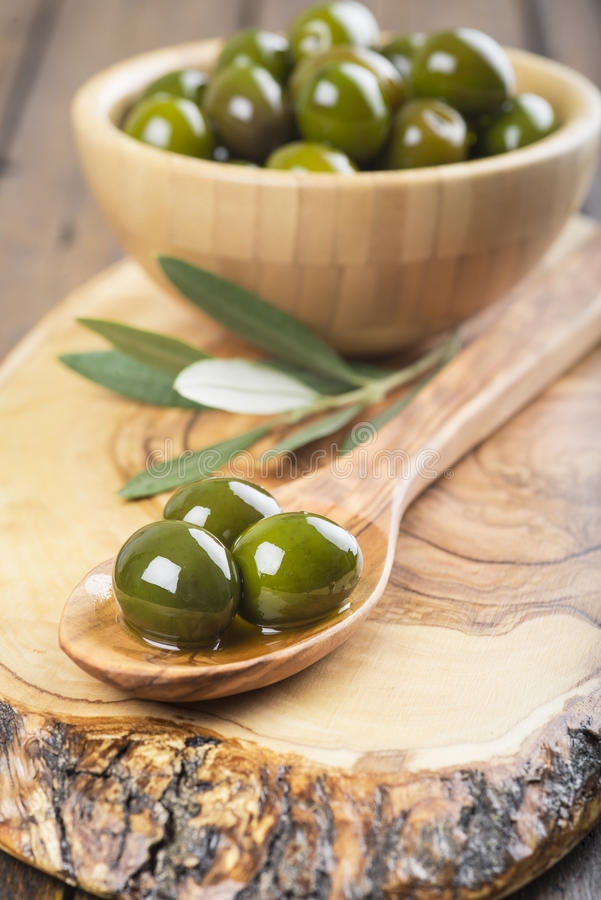 Wooden bowl and spoon with green olives and olive oil stock image