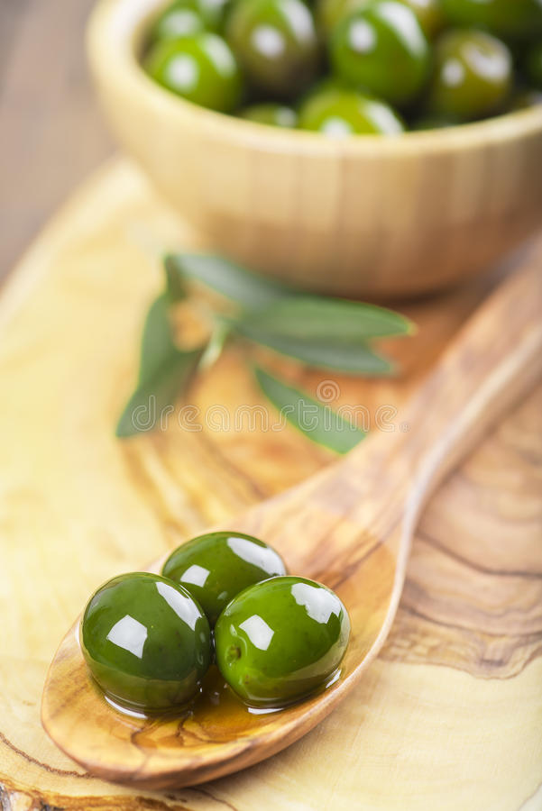 Wooden bowl and spoon with green olives and olive oil royalty free stock photo