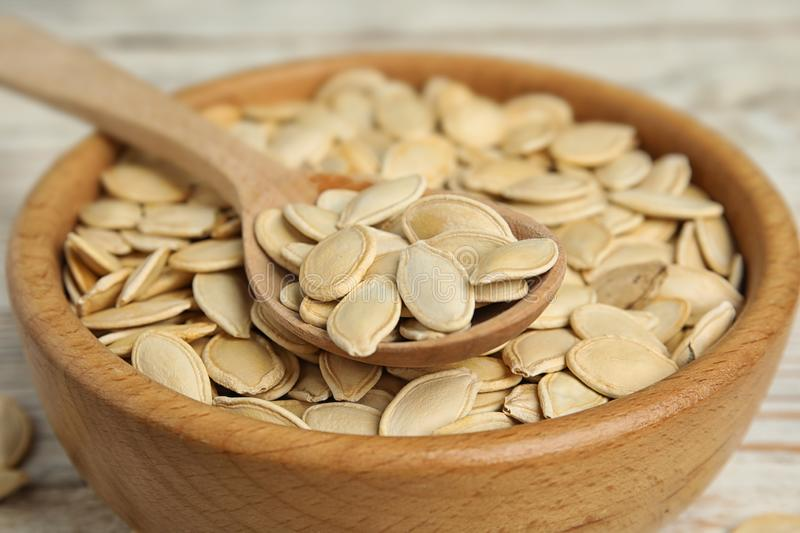 Wooden bowl and  of raw pumpkin seeds on white table, closeup. Wooden bowl and spoon of raw pumpkin seeds on white table, closeup stock image
