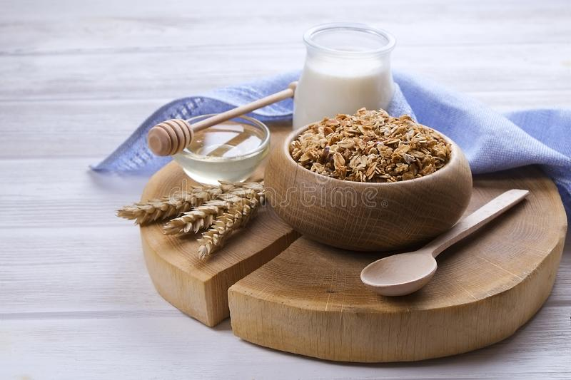 A wooden bowl of trail mix with almonds, raisins, seeds, cashew, hazelnut nuts, glass of milk and honey on white table. Vegetarian royalty free stock photos