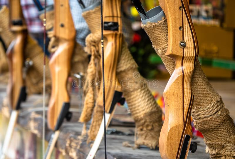 Wooden bows set up in a row at a shooting gallery at the fair, with a shallow depth of focus, weapon stock image
