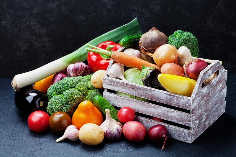 Wooden box with autumn harvest farm vegetables and root crops on black kitchen table. Healthy and organic food. stock photos