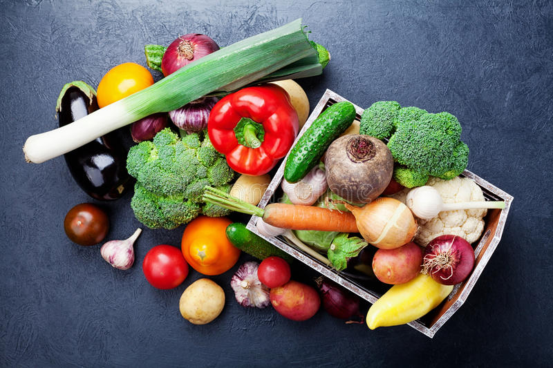 Wooden box with autumn harvest farm vegetables and root crops on black kitchen table top view. Healthy and organic food. stock photo