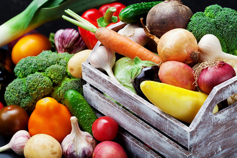 Wooden box with autumn harvest farm vegetables and root crops. Healthy and organic food background. Wooden box with autumn harvest farm vegetables and root royalty free stock photo