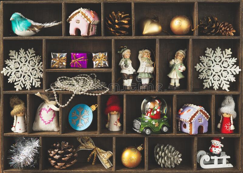 A wooden box with cells filled with small Christmas and New Year decor. stock photo