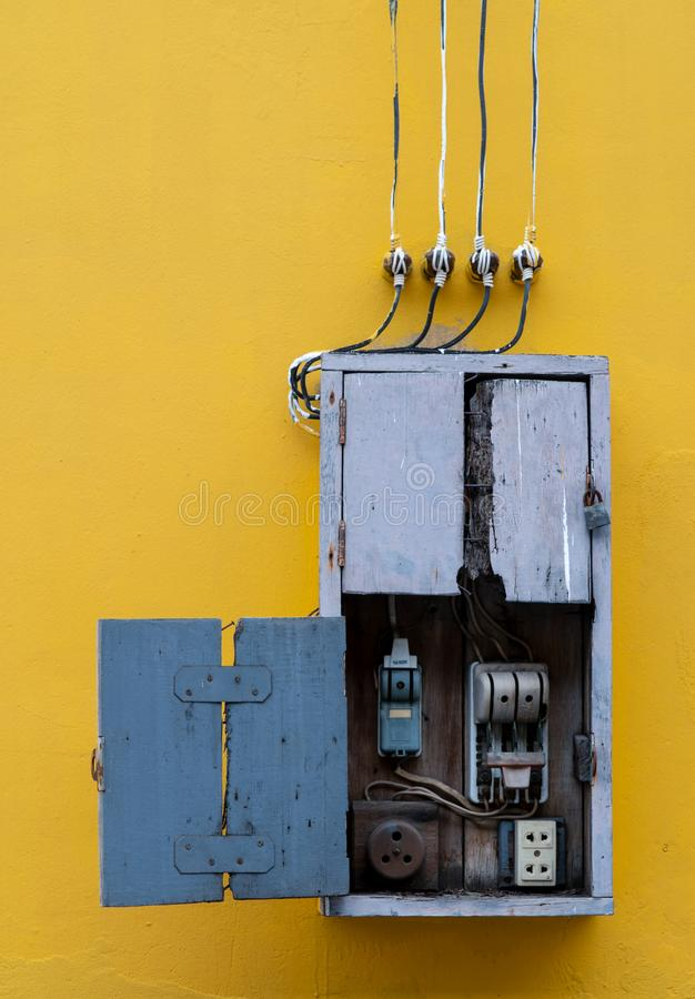 Wooden box, electric control equipment in the factory on yellow vintage concrete wall background. Manual cut out with old design. Safety in home and factory stock images