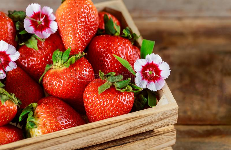 Wooden box of fresh ripe red strawberries on a farmers market royalty free stock images