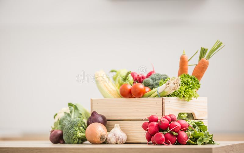 Wooden box full of fresh healthy vegetables. Broccoli carrot radish onion garlic corn on wooden kitchen table. Food, tomato, background, organic, green stock images
