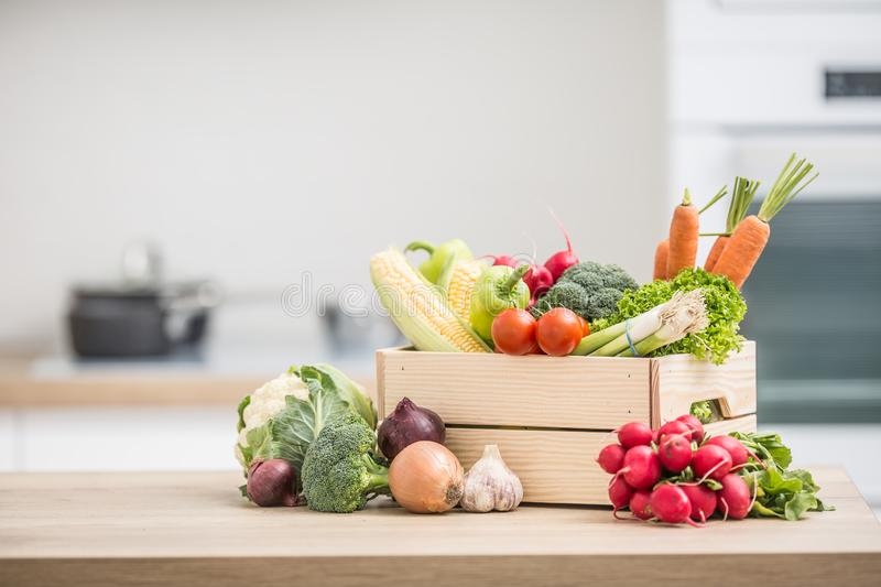 Wooden box full of fresh healthy vegetables. Broccoli carrot radish onion garlic corn on wooden kitchen table. Food, tomato, background, organic, green royalty free stock image