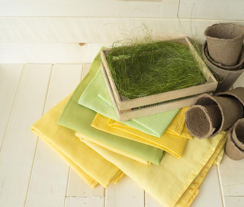 A wooden box with a grass. A ladder of towels and napkins. royalty free stock images