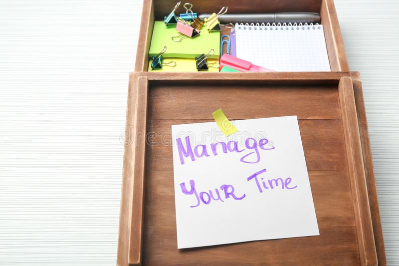 Wooden box with written phrase Manage your time on paper sheet and stationery on table. Time management concept royalty free stock image